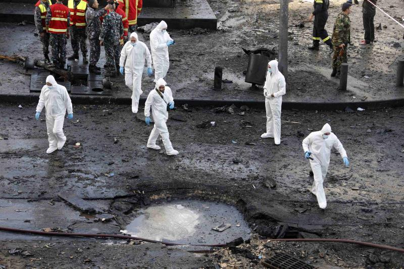 Forensic inspectors examine the site of the explosion in downtown Beirut