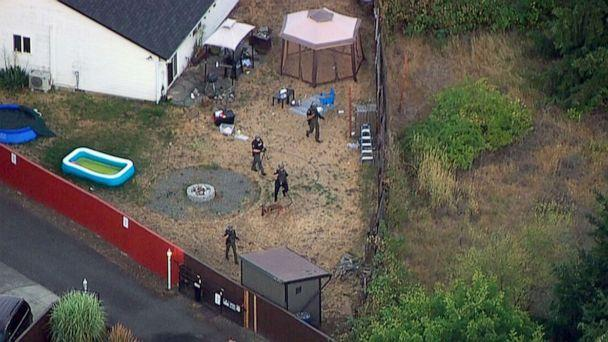 PHOTO: Law enforcement search the backyard of a home in pursuit of three suspects in the fatal shooting of a Clark County, Wash. Deputy Sheriff in Vancouver, B.C., Canada,  July 23, 2021 . (KATU)