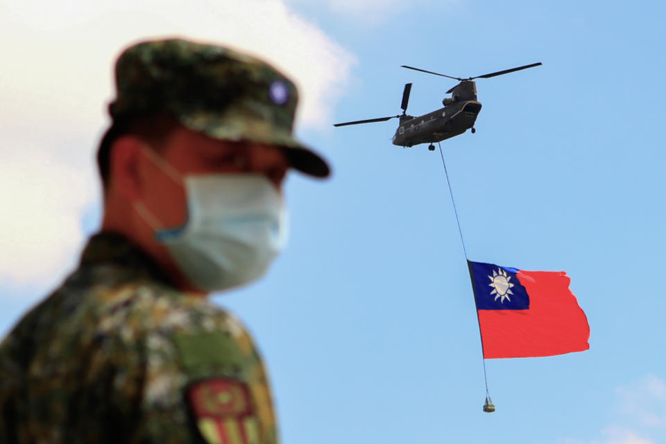 A Taiwanese soldier stands guard as a Chinook Helicopter carrying a Taiwan flag flies over a military camp, as part of a rehearsal for a National Day of Celebration in Taiwan last month. Source: Getty