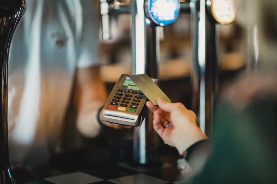 A close-up shot of an unrecognizable woman paying for a glass of red wine using contactless card payment at a bar.