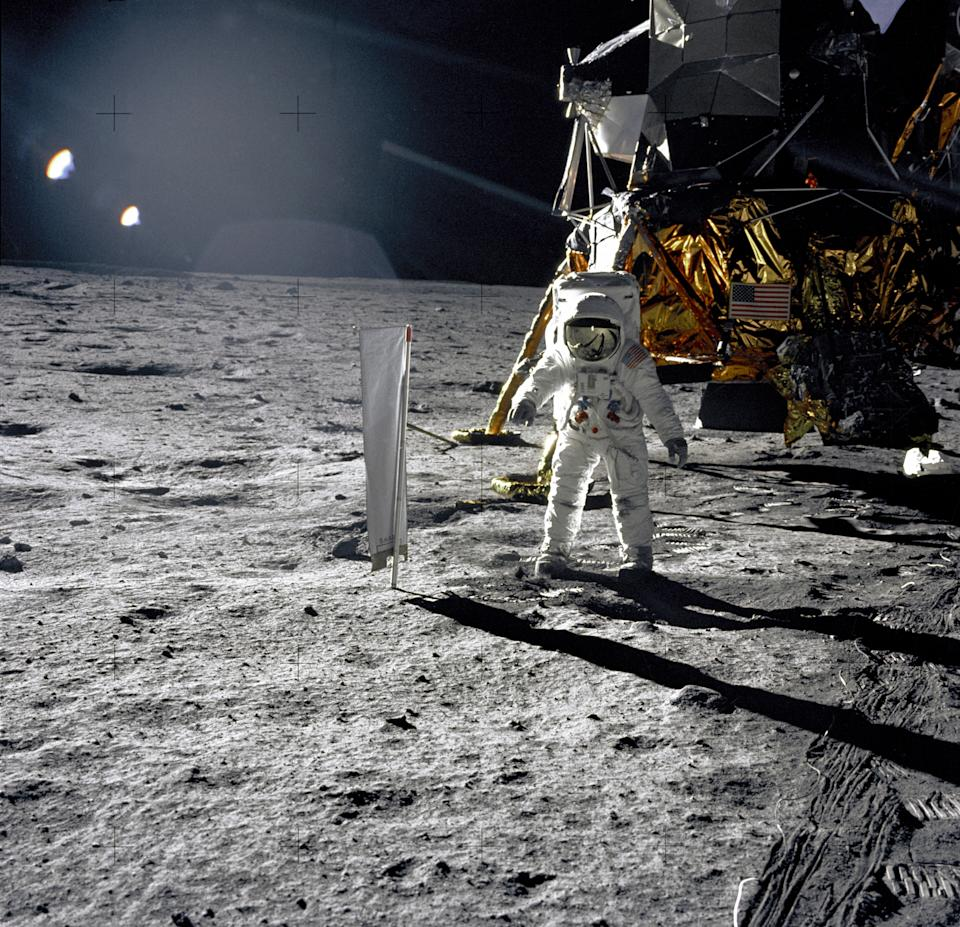 """Astronaut Edwin E. Aldrin, Jr., Lunar Module pilot, is photographed during the Apollo 11 extravehicular activity (EVA) on the lunar surface on July 20, 1969. In the right background is the Lunar Module """"Eagle."""" On Aldrin's right is the Solar Wind Composition (SWC) experiment already deployed. This photograph was taken by Neil A. Armstrong with a 70mm lunar surface camera. (Photo: NASA)"""