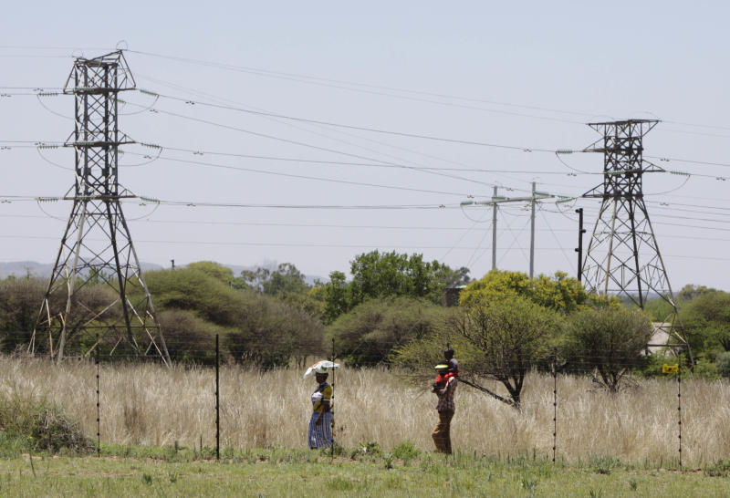 People walk below power pylons at Hartebeespoort, South Africa, Friday Nov. 25, 2011.  Eskom is Africa's biggest power utility, accounting for more than 60 percent of all the electricity generated on the continent, according to the World Bank. It also exports across southern Africa. Critics and even supporters say Eskom should have started its move toward renewable sources of energy earlier, and now needs to set its ambitions higher. (AP Photo/Denis Farrell)