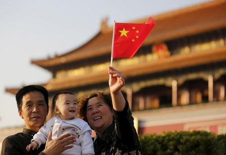 Guan Junze (C) and his grandparents take their souvenir picture in front of the Tiananmen Gate in Beijing November 2, 2015. REUTERS/Kim Kyung-Hoon/Files