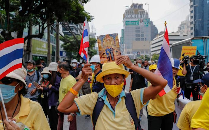 Supporters of the Thai monarchy came out wearing yellow and holding pictures of the king - AP Photo/Gemunu Amarasinghe