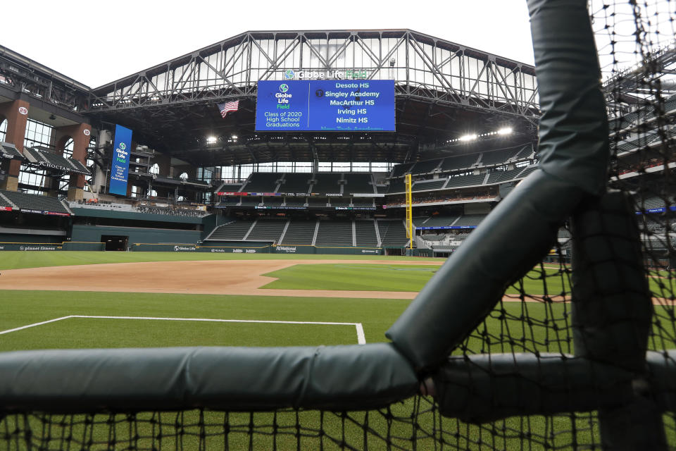 A view of the Globe Life Field, the newly-built home of the Texas Rangers, with the roof open from a perspective along the third base line is shown in Arlington, Texas, Wednesday, May 20, 2020. The large video screen at the top of the stadium shows upcoming high school graduation ceremonies for the class of 2020 to be held at the park. The Rangers were supposed to have its home opener on March 31, against the Los Angeles Angels, but have yet to see one game played in it this season amid the coronavirus pandemic. (AP Photo/Tony Gutierrez)
