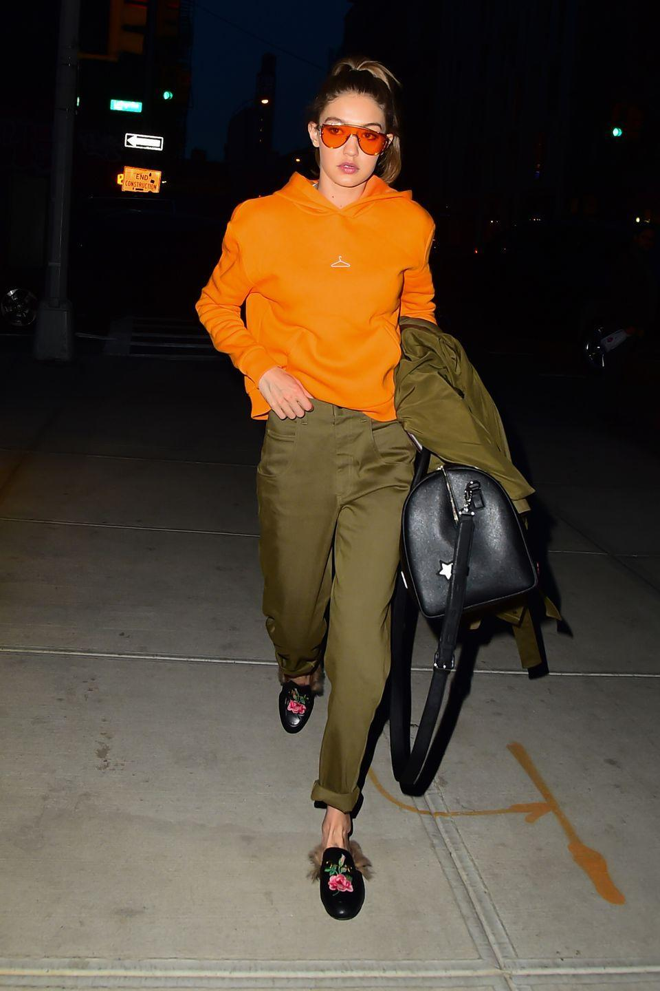 <p>In an orange hoodie, olive green trousers and matching jacket, Gucci loafers, black leather duffel bag and Gentle Monster orange tinted sunglasses while out in New York.</p>