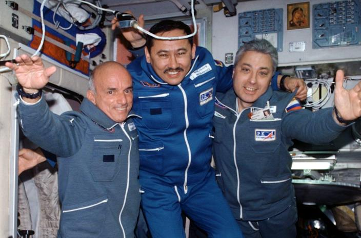 Three men floating in the International Space Station