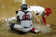 Philadelphia Phillies' Scott Kingery, right, cannot score past Atlanta Braves catcher Travis d'Arnaud on a fielder's choice by Rhys Hoskins during the 10th inning of a baseball game, Friday, Aug. 28, 2020, in Philadelphia. (AP Photo/Matt Slocum)