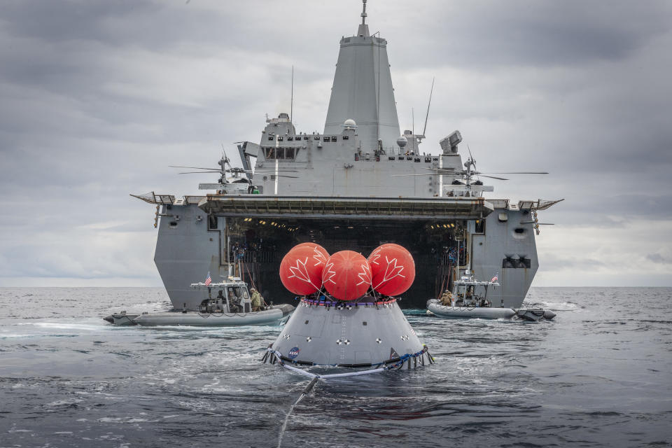 NASA's Orion crew capsule floats behind the USS John P. Murtha in the Pacific Ocean after the landing and recovery crews from the Exploration Ground Systems team at the agency's Kennedy Space Center performed their first full mission profile test of recovery procedures for the Artemis 1 mission, on March 13, 2020. Scheduled to launch in the second half of 2021, the Artemis 1 mission will mark the first uncrewed test flight of NASA's Space Launch System megarocket and Orion spacecraft.