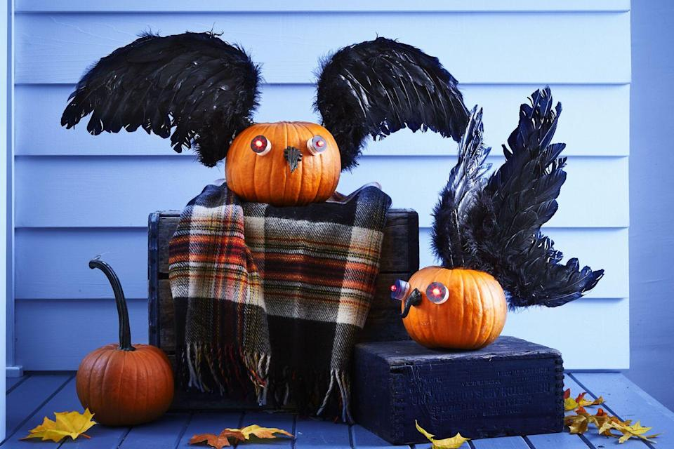 <p>Carefully remove the stem from a sugar pumpkin and paint it black. Trace bottoms of two waterproof red LED lights onto black paper, then cut out and punch hole in center; fit paper on lights.Hot-glue LED eyes and beak to pumpkin. Hot-glue wood skewers to backs of children's black feather angel wings; push into pumpkin to secure.</p>