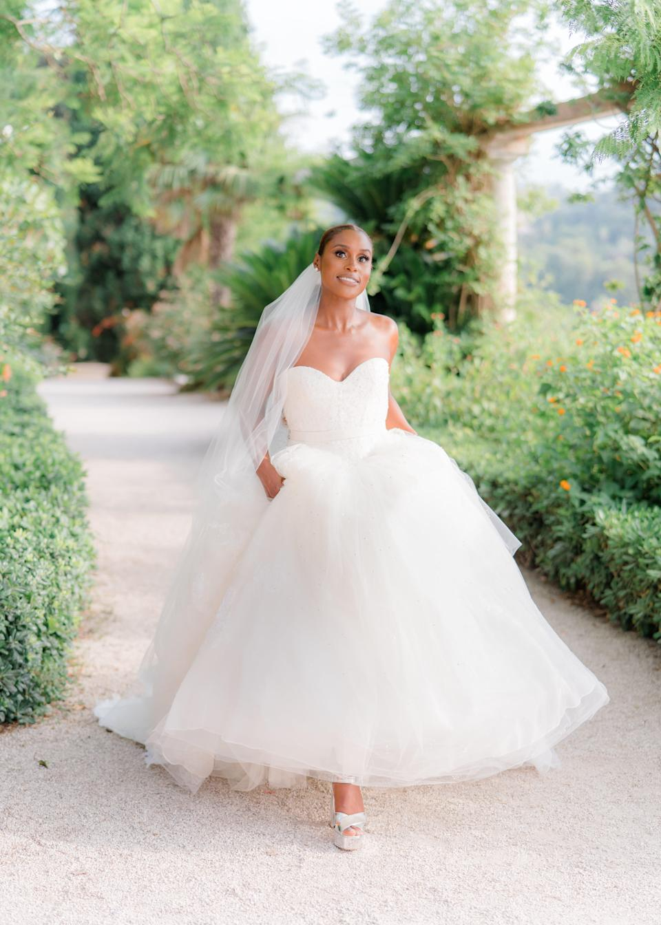 Issa Rae chose a custom light ivory strapless sweetheart neckline ballgown with hand placed Chantilly lace accented by hand sewn crystal beading and a light ivory chapel length veil with hand placed Chantilly lace.