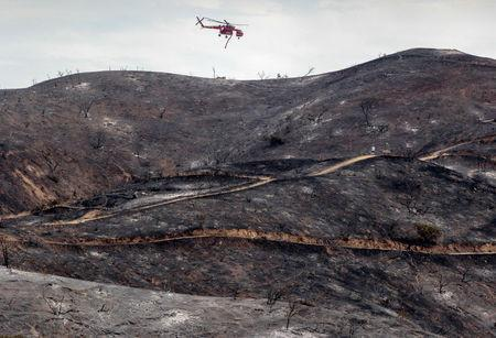 A fire helicopter flies over a charred hillside during the La Tuna Canyon fire over Burbank, California, September 3, 2017. REUTERS/ Kyle Grillot