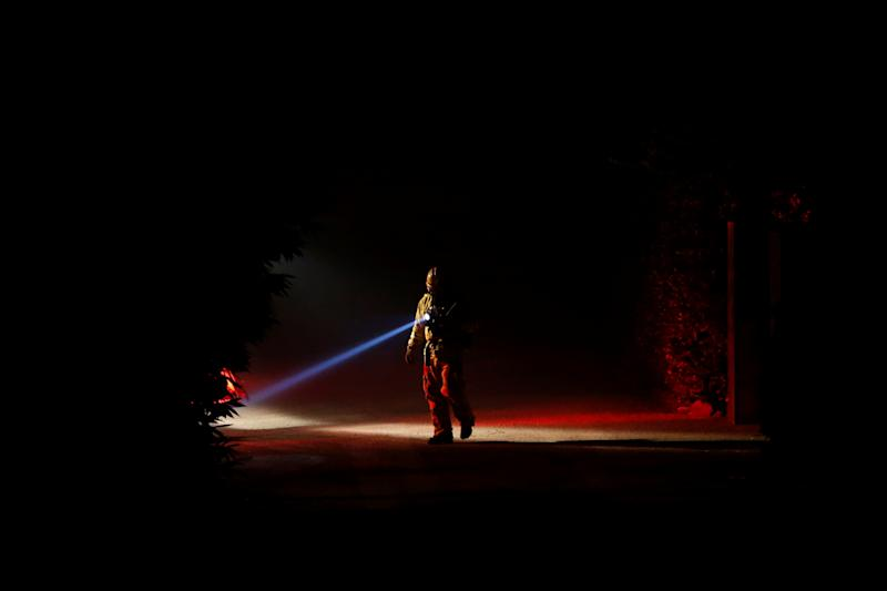 A firefighter with a flashlight is pictured as the wind driven Kincade fire burns near the town of Healdsburg, California, Oct. 27, 2019. (Photo: Stephen Lam/Reuters)