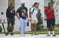Carolina Panthers players, from left, safety Sam Franklin, defensive end Brian Burns, defensive end Yetur Gross-Matos and defensive end Marquis Haynes wait outside the team's dormitory at NFL football training camp, Tuesday, July 27, 2021, at Wofford College in Spartanburg, S.C. (Jeff Siner/The Charlotte Observer via AP)