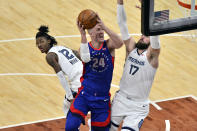 Detroit Pistons center Mason Plumlee (24) shoots between Memphis Grizzlies center Jonas Valanciunas (17) and guard Ja Morant (12) during the second half of an NBA basketball game Friday, Feb. 19, 2021, in Memphis, Tenn. (AP Photo/Brandon Dill)