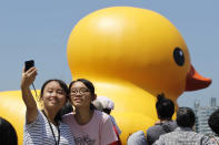Two girls take a portrait in front of a giant yellow duck at the Glory Pier in the port of Kaohsiung, Taiwan, Thursday, Sept. 19, 2013. Putting up with the high temperatures, thousands flocked to the port of Kaohsiung, the first leg of the Taiwan tour, to see Dutch artist Florentijn Hofman's famous 18 meter (59 foot) yellow duck, a gigantic version of the iconic bathtub toy used by children around the world. (AP Photo/Wally Santana)