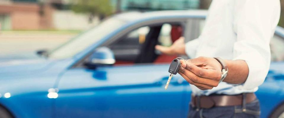 Male hand holding car keys offering new blue car in the background
