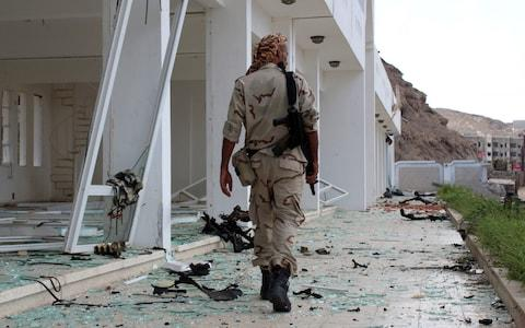 A fighter from the separatist Southern Transitional Council gather on February 25, 2018, at the site of two suicide car bombings - Credit: AFP