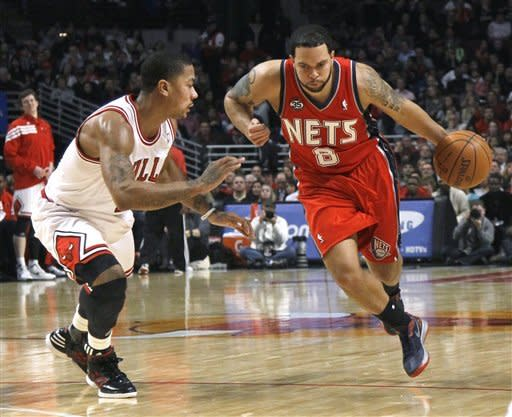 New Jersey Nets guard Deron Williams (8) drives on Chicago Bulls guard Derrick Rose during the first half of an NBA basketball game Monday, Jan. 23, 2012, in Chicago. (AP Photo/Charles Rex Arbogast)