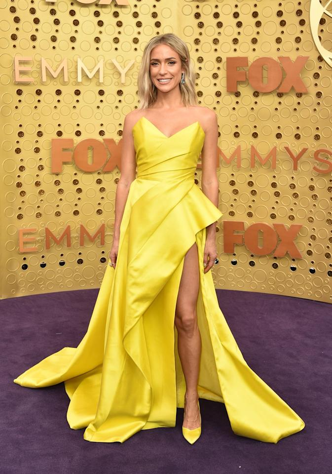 <p>Wearing a structural yellow gown with a thigh-high slit. </p>