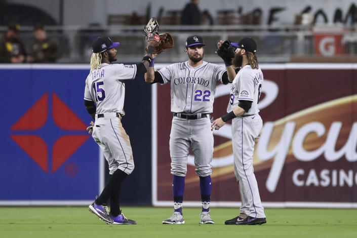 Colorado Rockies outfielders Raimel Tapia, left, Sam Hilliard (22) and Charlie Blackmon celebrate after the Rockies defeated the San Diego Padres in a baseball game Friday, July 30, 2021, in San Diego. (AP Photo/Derrick Tuskan)