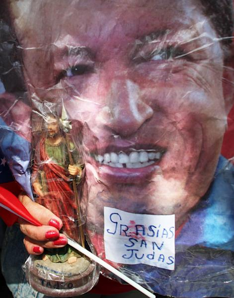 "A supporter of Venezuela's President Hugo Chavez attends a celebration marking the leader's return, in Bolivar Square, in Caracas, Venezuela, Monday, Feb. 18, 2013. The woman holds a cutout image of Chavez along with a Saint Judas statue and a note that reads in Spanish: ""Thank you St. Judas,"" because she believes her prayers to the Catholic saint helped in the return of the ailing president. Chavez returned to Venezuela early Monday after more than two months of medical treatment in Cuba following cancer surgery, and was being treated at the Carlos Arvelo Military Hospital in Caracas, his government said. (AP Photo/Fernando Llano)"