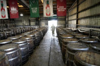 David Botkin, a mash warehouse technician, walks among barrels of Tabasco pepper mash that is being aged, at the McIlhenny Company on Avery Island, La., Tuesday, April 27, 2021. The company has been brewing Tabasco Sauce since 1868 on Avery Island — the tip of a miles-deep column of salt — and now fills up to 700,000 bottles a day, selling them in 195 countries and territories. (AP Photo/Gerald Herbert)