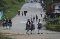 Wearing masks to curb the spread of the new coronavirus, students walk to the one open school in Campohermoso, Colombia, Thursday, March 18, 2021. Campohermoso is one of two municipalities in Colombia that has not had a single case of COVID-19 since the pandemic started one year ago, with the student body at the school rotating half the students into their classrooms while the other attends via the internet. (AP Photo/Fernando Vergara)