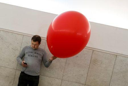 A man uses his mobile phone as he sells balloons at a subway station in Moscow, Russia June 30, 2018. REUTERS/Gleb Garanich