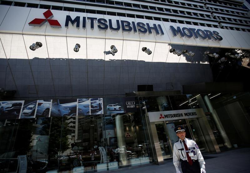 A security personnel walks in front of Mitsubishi Motors Corp's headquarters in Tokyo, Japan