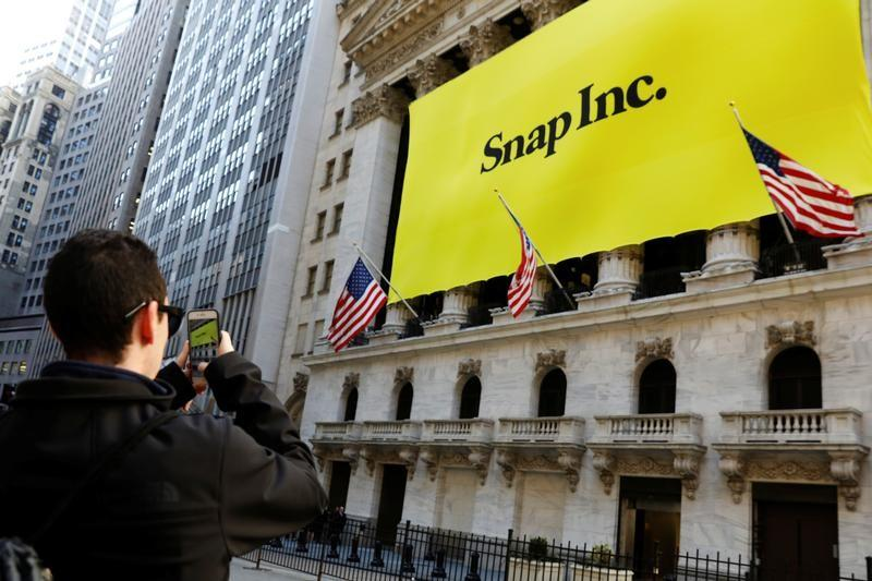 A man takes a photograph of the front of the New York Stock Exchange (NYSE) with a Snap Inc. logo hung on the front of it shortly before the company's IPO in New York