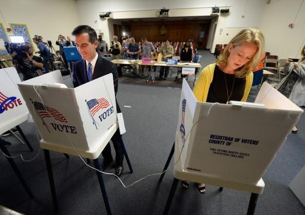 Eric Garcetti and Amy Wakeland complete their ballots inside voting booths.