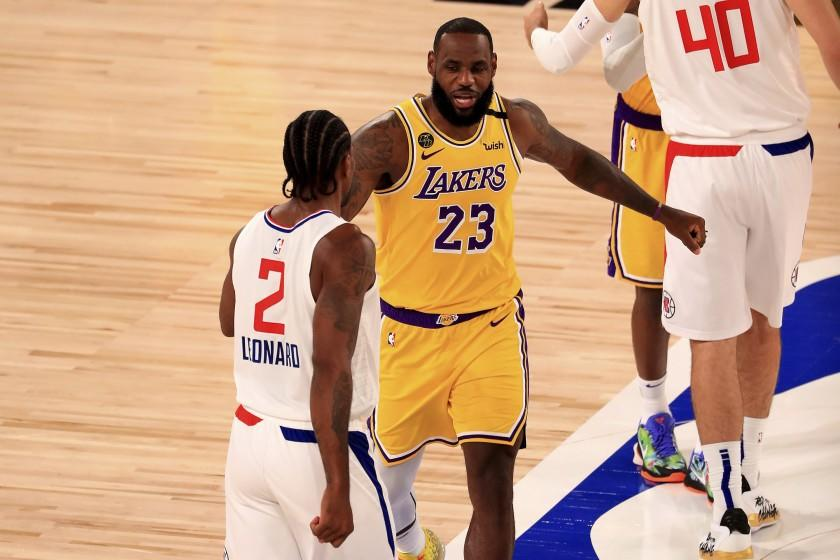 Los Angeles Lakers' LeBron James (23) talks with Los Angeles Clippers' Kawhi Leonard.