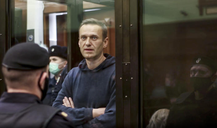 In this handout photo taken from a footage provided by Moscow City Court, Russian opposition leader Alexei Navalny stands in the cage during a hearing to a motion from the Russian prison service to convert the suspended sentence of Navalny from the 2014 criminal conviction into a real prison term in the Moscow City Court in Moscow, Russia, Tuesday, Feb. 2, 2021. A Moscow court has ordered Russian opposition leader Alexei Navalny to prison for more than 2 1/2 years for violating the terms of his probation while he was recuperating in Germany from nerve-agent poisoning. Navalny, who is the most prominent critic of President Vladimir Putin, had earlier denounced the proceedings as a vain attempt by the Kremlin to scare millions of Russians into submission. (Moscow City Court via AP)
