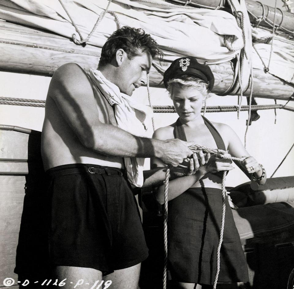 <p>Errol Flynn and Rita Hayworth match one another in high-waisted black shorts. The actress pairs hers with a black halter bikini top and a sailing cap, as Flynn shows her a sailing knot. </p>