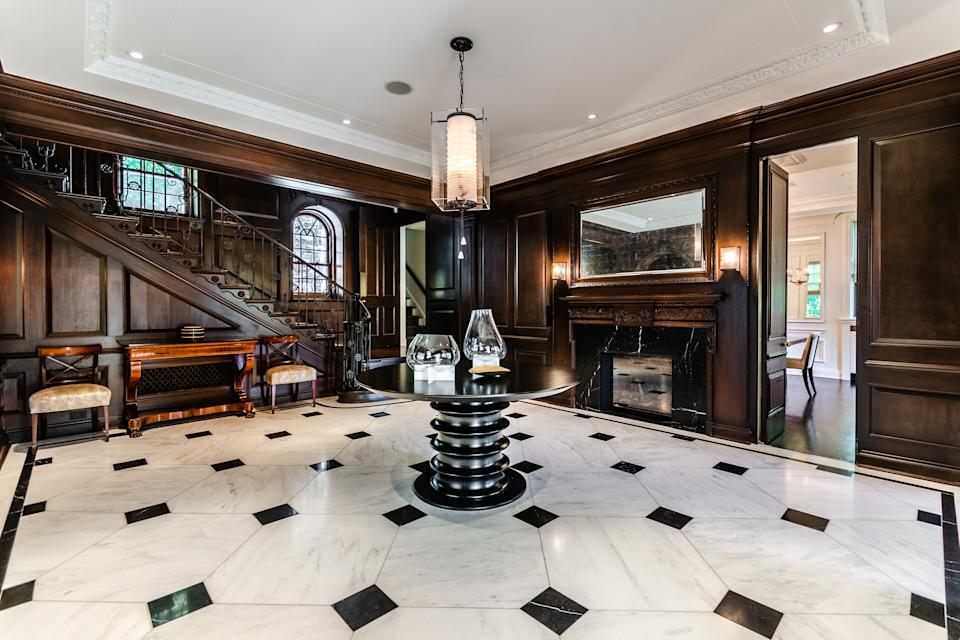 The wide open entry way features intricate moldings and lots of deep, rich wood. There's even a gas fireplace.