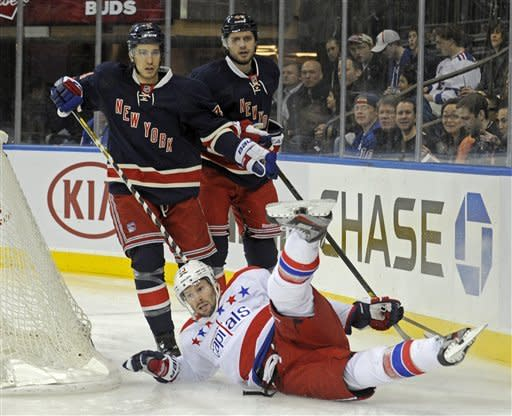 Washington Capitals' Troy Brouwer hits the ice in front of New York Rangers' Michael Del Zotto, left, and Steve Eminger, top right, during the first period of an NHL hockey game Sunday, March 24, 2013, at Madison Square Garden in New York. (AP Photo/Bill Kostroun)