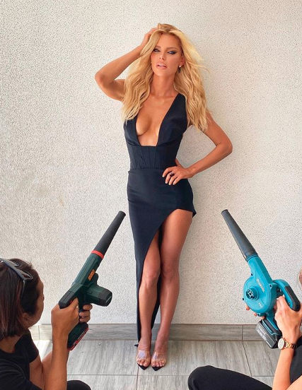 Sophie Monk in a black low cut dress with people use leaf blowers