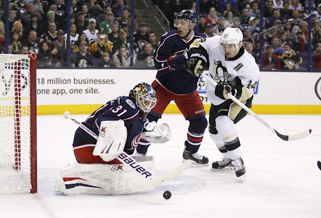 Columbus Blue Jackets goalie Curtis McElhinney (31) blocks a shot as Pittsburgh Penguins' Chris Kunitz (14) moves in while being defended by Jack Johnson (7) during the first period of an NHL hockey game, Friday, March 28, 2014, in Columbus, Ohio. (AP Photo/Mike Munden)