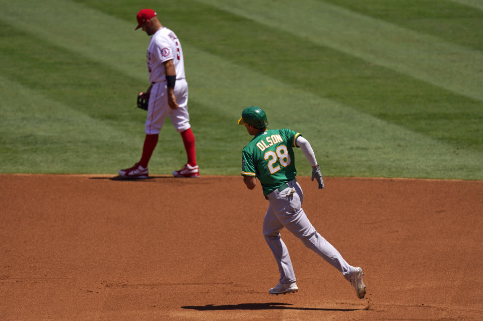 Oakland Athletics' Matt Olson, right, passes Los Angeles Angels first baseman Albert Pujols as he rounds first after hitting a solo home run during the first inning of a baseball game Wednesday, Aug. 12, 2020, in Anaheim, Calif. (AP Photo/Mark J. Terrill)