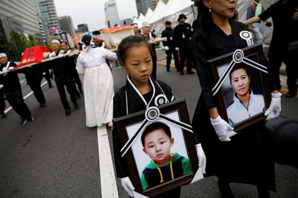 PHOTO: A girl and her North Korean defector mother hold portraits of a 42-year-old defector mother and her 6-year-old son who were found dead of starvation in Seoul, South Korea, Sept. 21, 2019. (Kim Hong-ji/Reuters)