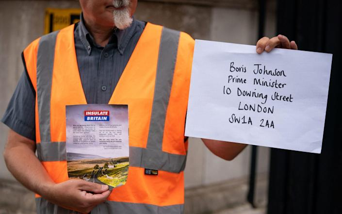 A member of Insulate Britain attempts to hand in a letter for Boris Johnson at Downing Street - PA