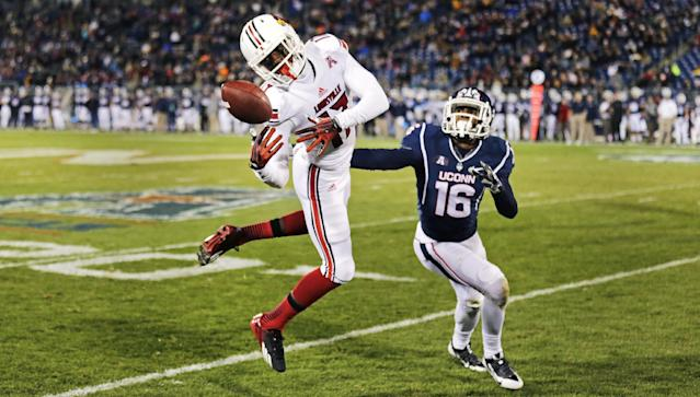 Louisville wide receiver James Quick (17) attempts to get a grip on the ball as Connecticut's Byron Jones (16) defends during the first half of an NCAA college football game, in East Hartford, Conn., Friday, Nov. 8, 2013. (AP Photo/Charles Krupa)