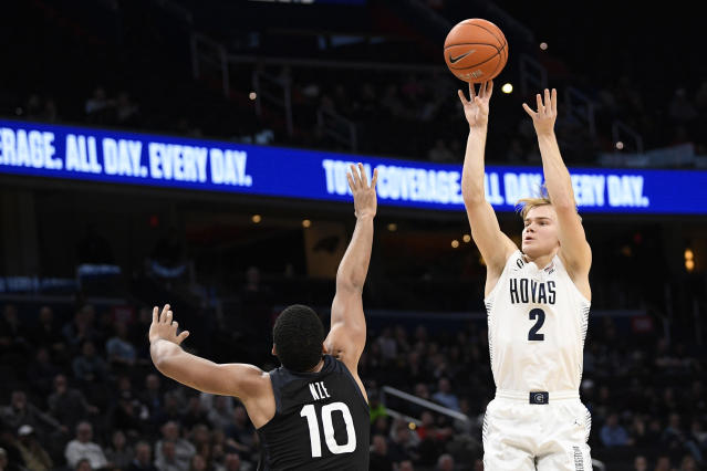 FILE - In this Tuesday, Jan. 28, 2020, file photo, Georgetown guard Mac McClung (2) shoots as he is defended by Butler forward Bryce Nze (10) during the second half of an NCAA college basketball game, in Washington. McClung announced Wednesday, May 13, 2020, that he plans to enter the NCAA transfer portal so he can switch schools after taking his name out of consideration for the NBA draft. (AP Photo/Nick Wass, File)