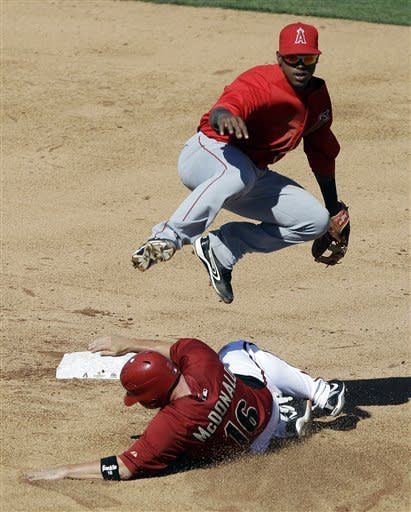 Los Angeles Angels shortstop Jean Segura, top, turns a double play over Arizona Diamondbacks' John McDonald on a ground ball by Aaron Hill during the sixth inning of a spring training baseball game Tuesday, March 13, 2012, in Scottsdale, Ariz. (AP Photo/Marcio Jose Sanchez)