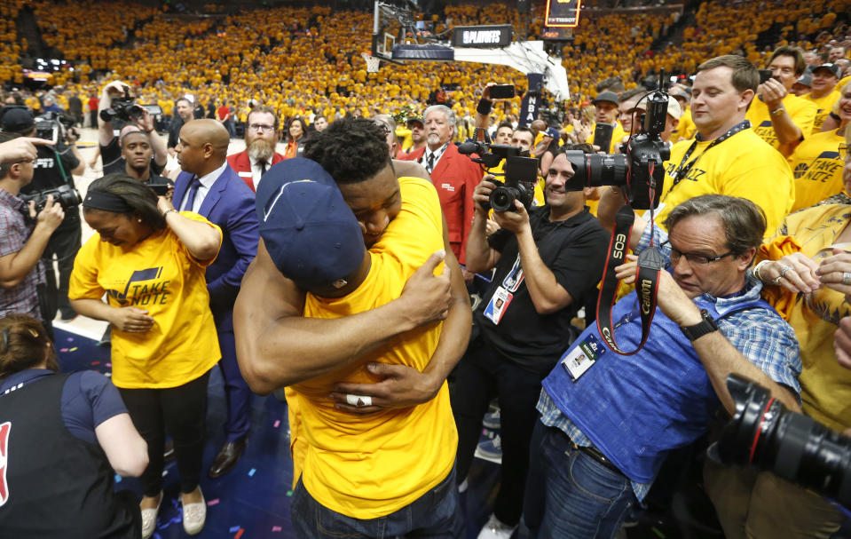 FILE - In this April 27, 2018, file photo, Utah Jazz guard Donovan Mitchell, center, hugs his father as he walks off the court following Game 6 of an NBA basketball first-round playoff series in Salt Lake City. Mitchell Sr., who works for the New York Mets, has tested negative for the coronavirus. Mitchell Sr. is the Mets director of player relations and community outreach. The younger Mitchell confirmed Thursday, March 12, 2020, he tested positive for the virus after Jazz teammate Rudy Gobert became the first NBA player to test positive, with Gobert's result prompting the league to suspend the season. (AP Photo/Rick Bowmer, File)