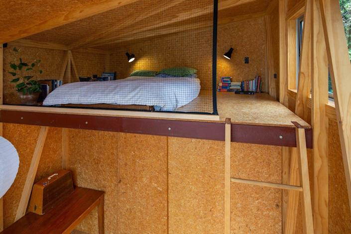 A cozy upper loft in the garden studio features a mattress for reading.