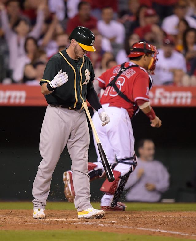 Oakland Athletics' Josh Donaldson, left, tosses his bat after striking out as Los Angeles Angels catcher Hank Conger runs off the field during the sixth inning of a baseball game, Tuesday, June 10, 2014, in Anaheim, Calif. (AP Photo/Mark J. Terrill)