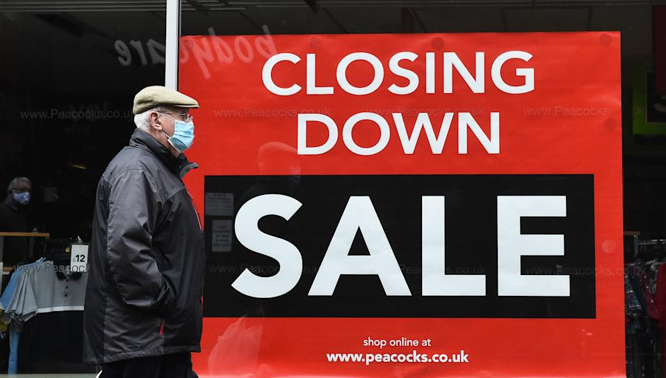 NEWCASTLE-UNDER-LYME, ENGLAND - NOVEMBER 20: A man walks past a branch of Peacocks clothing store on November 20, 2020 in Newcastle-Under-Lyme, England. The chain is among a number of businesses to announce their closure, blaming the inability to survive the financial impact of national lockdowns and social restrictions. (Photo by Nathan Stirk/Getty Images)