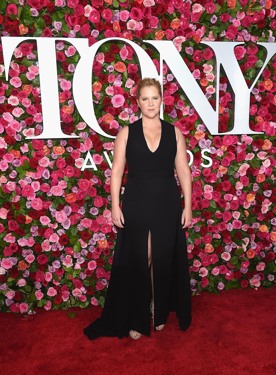 <p>Comedienne Amy Schumer went simple in a plunging black gown with a split.<em> [Photo: Getty]</em> </p>